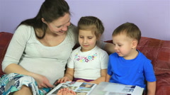 Mom with kids consider an album with photos. Happy family waiting for third - stock footage