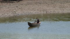 Boy paddling in wooden canoe on river Stock Footage
