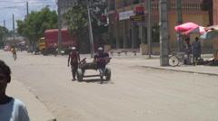 Boy pulling cart on dusty village road Stock Footage