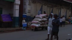 Boys loading big bags onto a wooden cart on street in Madagascar highland Stock Footage