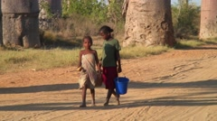 Children walking with plastic buckets in their hand on road in front of Baobabs Stock Footage