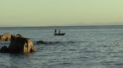 Fishermen standing in wooden boat with wooden paddle on the ocean fishing Stock Footage