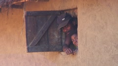 Man and girl looking out of window traditional madagascan  two story house Stock Footage