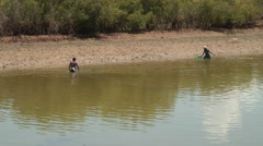 Man and woman walking in muddy river fishing with fishernet Stock Footage