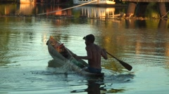 Man fishing in wooden canoe with net in river in afternoon sun Stock Footage