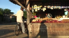 Man on bicycle at market stall in bright afternoon stall in village Stock Footage