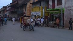 Men transport goods and people in madagascan rickshaws in the highland village Stock Footage