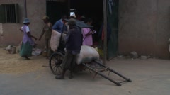Mill factory workers tie bick sacks of grains on wooden old rickshaw Stock Footage