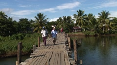People crossing wooden bridge over river and girl carry plastic basket on head Stock Footage