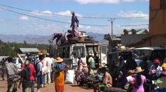 Street life in Madagascar highland with man standing on buss loading Stock Footage