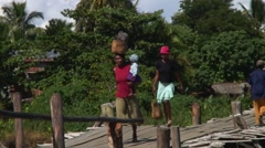 Woman crossing wooden bridge with bag on her head and baby on her arm Stock Footage