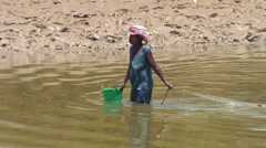 Woman with hat draging fishing net after herself in muddy river Stock Footage