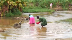 Women washing clothes by hand in river Stock Footage