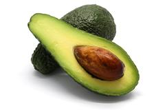 One whole and one sliced avocado - stock photo