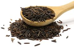 Wild rice in a wooden spoon Stock Photos