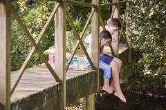 Brother and sister dangling bare feet over edge of footbridge - stock photo