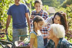 Stock Photo of Multi-generation family bonding in sunny garden