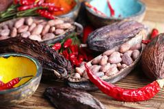 Cacao beans and chili peppers Stock Photos