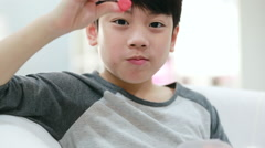 Shot of asian cute boy eating a lollipop with funny face expressions. Stock Footage