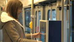 Young woman buying ticket from vending machine on the tram Stock Footage