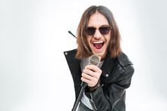 Happy young man with long hair  using microphone for singing - stock photo