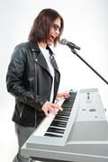 Charismatic young man playing on synthesizer and singing in microphone - stock photo