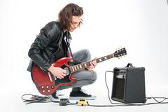 Focused handsome young guitarist playing electric guitar with amplifier - stock photo