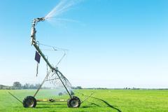 Spray water machine in grassland Stock Photos