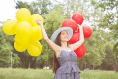 Happy Beautiful Carefree Young Woman with Red and Yellow Balloons. Attractive Stock Photos