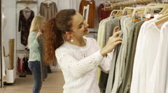 Happy young girls choosing new clothes in shop - stock footage