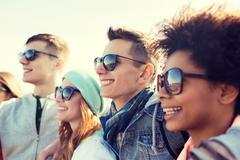 Stock Photo of happy teenage friends in shades hugging outdoors