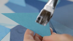 Gluing blue triangle paper on collage Stock Footage