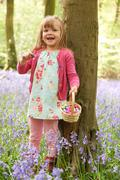 Girl On Easter Egg Hunt In Bluebell Woods Stock Photos