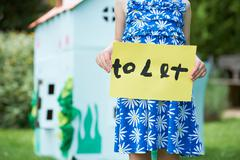 Little Girl Holding To Let Sign Outside Play House Stock Photos