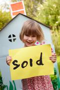 Little Girl Holding Sold Sign Outside Play House Stock Photos