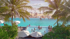 Tourists enjoying a resort's swimming pool, overlooking a tropical beach Stock Footage