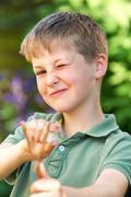 Boy Aiming Slingshot In Garden Stock Photos