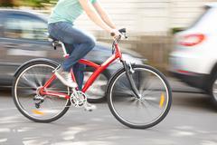 Cyclist At Speed Along Urban Street - stock photo