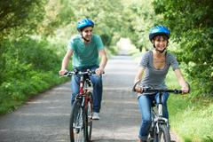 Young Couple Cycling Along Country Lane - stock photo