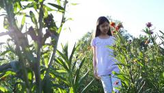 Happy Asian girl walking in the flower field with sunlight, Slow motion shot Stock Footage