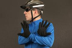 cyclist looking to the side and shows a negative sign with hands - stock photo