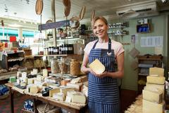 Owner Of Delicatessen Standing In Shop Holding Cheese Stock Photos