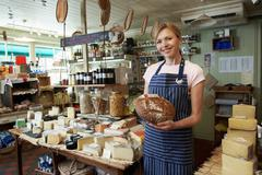 Owner Of Delicatessen Standing In Shop Holding Loaf Stock Photos
