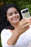 Young Woman Lying On Grass Sending Text Message Stock Photos