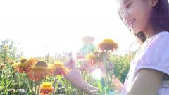 Happy Asian girl holding the flower in the field with sunlight, Slow motion shot Stock Footage