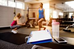 Stock Photo of Gym details, women exercising, clipboard, water bottle, smart ph