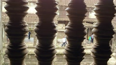 Unique perspective shot through ornate railing of tourists at Angkor Wat Stock Footage