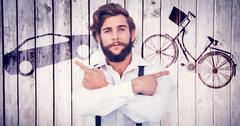 Composite image of confident hipster pointing sideways with arms crossed - stock photo