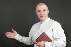 white man with the pen and the book indicates with his hand towards - stock photo