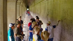Tour guide explains relief carvings along corridor wall in Angkor Wat Stock Footage